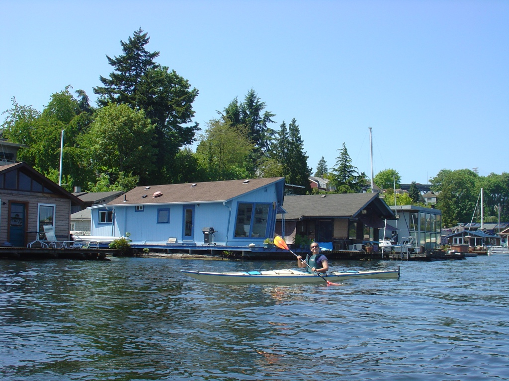 b. kayaking by a cute turquoise houseboat